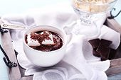 Hot chocolate with marshmallows in mug, on tray, on color wooden background