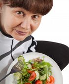 Pension age good looking woman eating  salad