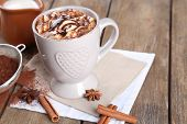 Cup of hot coffee with marshmallow and cup of milk with cinnamon, star anise and strainer of cocoa on napkin and rustic wooden table background