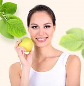 Beautiful young woman with green apple on light background