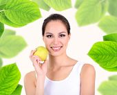 Beautiful young woman with green apple in frame made from leaves