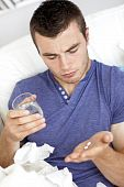 stock photo of young men  - Depressed Young Man Taking Pills With Water in the living - JPG
