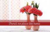 Beautiful flowers in vases with light from window and space for your text