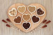 Brown sugar with crystal lollipops in abstract design on a wooden heart shaped board over bamboo background.