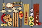 Italian food ingredients with pasta, herb and spice selection, over grey wooden background.