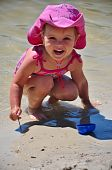 Little girl in pink cowboy hat on the beach