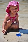 Little toddler girl playing on the beach
