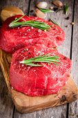 foto of cutting board  - two raw steaks with rosemary garlic salt and pepper in olive cutting board - JPG