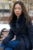 serious Asian girl in blue coat looks right