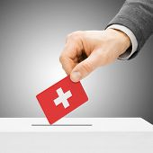 Voting Concept - Male Inserting Flag Into Ballot Box - Switzerland