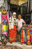 BANGKOK, THAILAND, DECEMBER 26, 2013: Senior tourist poses with the owner of small store selling and hiring clothes suitable for visiting temples