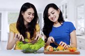 Asian Women Cooking Salad In Kitchen
