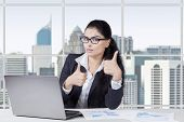 picture of indian  - Successful indian businesswoman showing thumbs up in the office while working with laptop - JPG