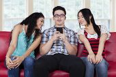 stock photo of curio  - Portrait of caucasian person sitting on sofa with curios girls looking at his smartphone - JPG