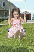 A Happy Little Girl Smiling on Swing