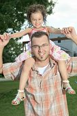 father and daughter.Young man holding a little girl on shoulders