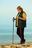 Active Woman Senior Nordic Walking On A Beach