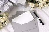 foto of writing  - Writing paper or wedding invitation with envelope laid on bridal lace with several wedding gifts and white rose bouquets - JPG