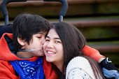 Disabled Little Boy Kissing His Big Sister On Cheek While Seated In Wheelchair