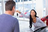 Smiling woman holding her new key at new car showroom