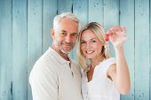 Happy couple showing their new house key against wooden planks