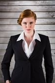 Stylish redhead businesswoman in suit against wooden planks