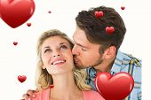 Handsome man kissing girlfriend on cheek against hearts