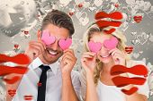 Attractive young couple holding pink hearts over eyes against grey valentines heart pattern