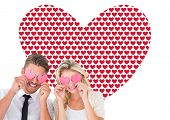 Attractive young couple holding pink hearts over eyes against valentines day pattern
