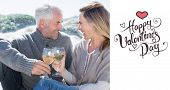 Couple enjoying white wine on picnic at the beach against happy valentines day