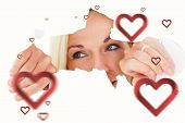 Blonde woman looking through torn paper against hearts