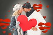 Smiling couple in winter fashion posing with heart shape against white background with vignette