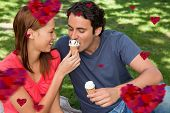 Woman feeding her friend ice cream against hearts