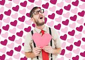 Geeky hipster crying and holding heart card against valentines day pattern
