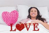 Woman lying in her bed next to a pink heart pillow against love spelled out in petals