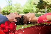 Two friends looking upwards while lying head to head against valentines heart design