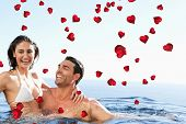 Couple enjoying time together in the pool against valentines heart design