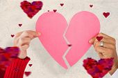 Couple holding two halves of broken heart against parchment
