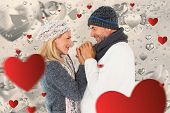 Couple in winter fashion embracing against grey valentines heart pattern