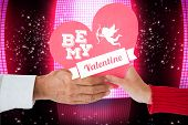 Couple holding heart against glittering screen on black background