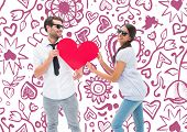 Hipster couple smiling at camera holding a heart against valentines pattern