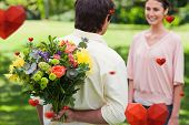 Man about to present a bouquet of flowers to his friend against hearts