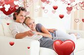 Couple cuddling while watching TV against love heart pattern