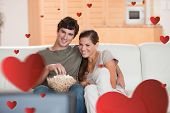 Couple with popcorn on the sofa watching a movie against hearts