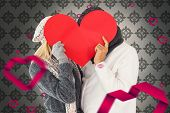 Couple in winter fashion posing with heart shape against grey wallpaper