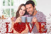 Couple looking at the camera with a coffee against love spelled out in petals