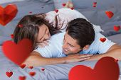 Couple having fun on the bed against love heart pattern
