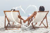 smoke heart against couple lying on deck chairs