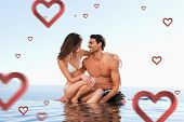 Couple sitting on pool edge together against hearts