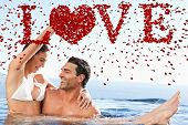 Happy couple enjoying time together in the pool against love spelled out in petals